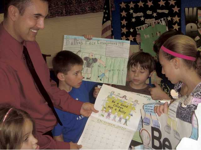 Bouquet Canyon Elementary School Principal Jeff Pettipas, left, shows students the completed 2010 calendar made by Saugus Union School District children. Each month includes a student drawing that promotes anti-bullying.