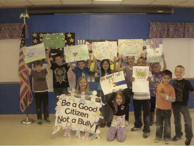 Bouquet Canyon Elementary School kids show off their posters of ways to stop bullying at school. Saugus Union School District children recently put together calendars with each month describing a way to stop bullying and promote friendships.