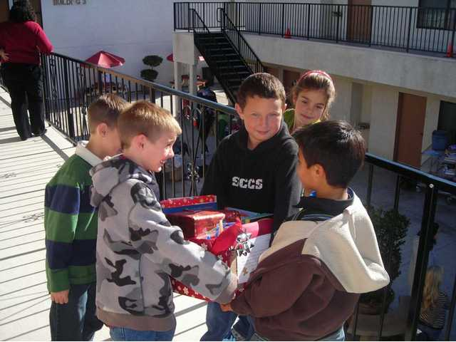 Santa Clarita Christian School third-graders Nathan Stabe, far left, Ben Wyllie, Daryll Michaelis and Julia Philipps give a box of books to classmate Josiah Jimenez, far right.