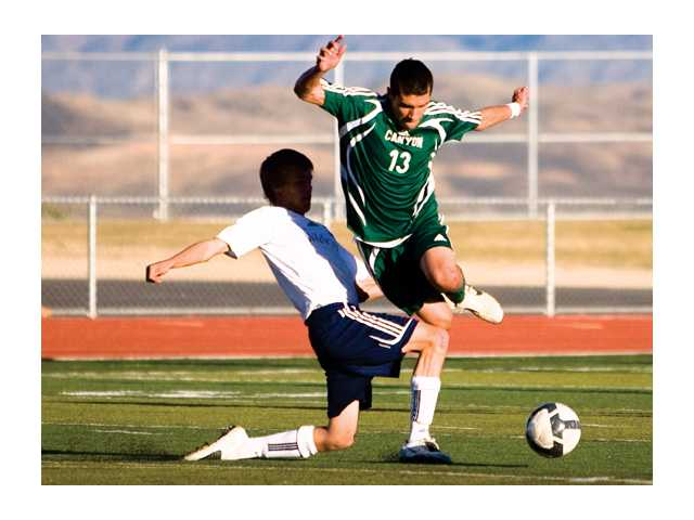 Canyon midfielder David Perez (13) jumps over West Ranch's Cameron Nelson Tuesday at West Ranch High. Canyon won the game 2-1.