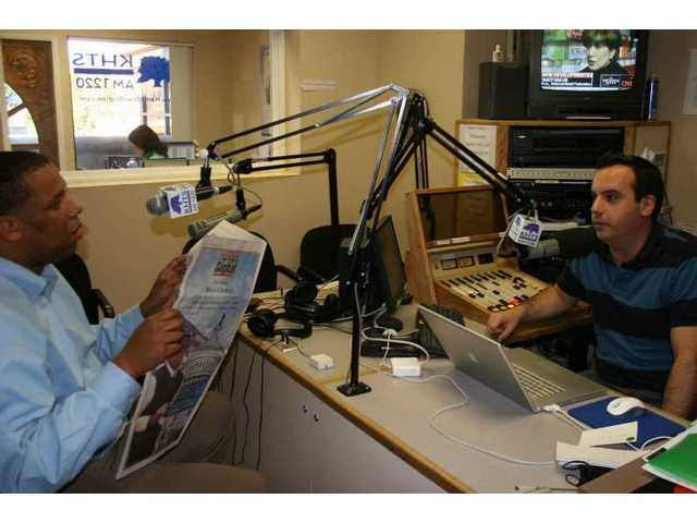"Signal Staff Reporter Brian Charles (left) refers to a ""Washington Journal: the Inauguration"" story he wrote in the paper as he fields a question from KHTS AM 1220 afternoon drive host Jason Endicott (right)."
