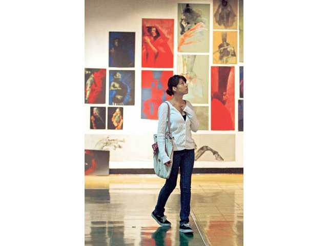Photography student Jessica Castillo, 18, walks through a Hunchback of Notre Dame art exhibit at the California Arts Institute Thursday afternoon on January 15.