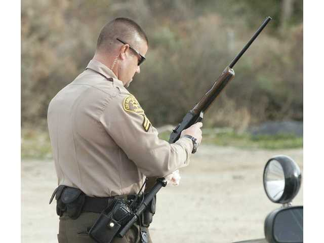 A Santa Clarita Sheriff's deputy examines a realistic-looking BB gun after they arrested a 48-year-old man at gunpoint.