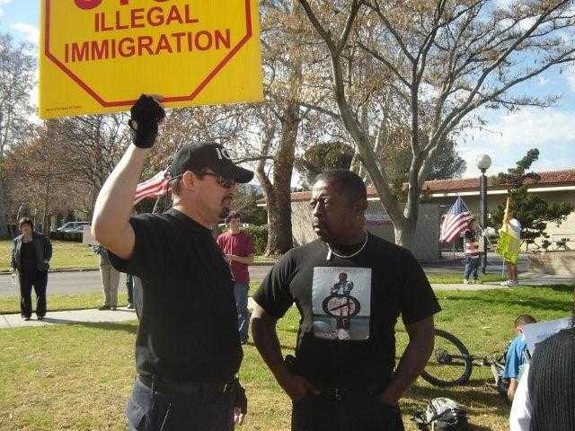 Jamiel Shaw speaks with another protester at the anti-illegal alien rally on Saturday.
