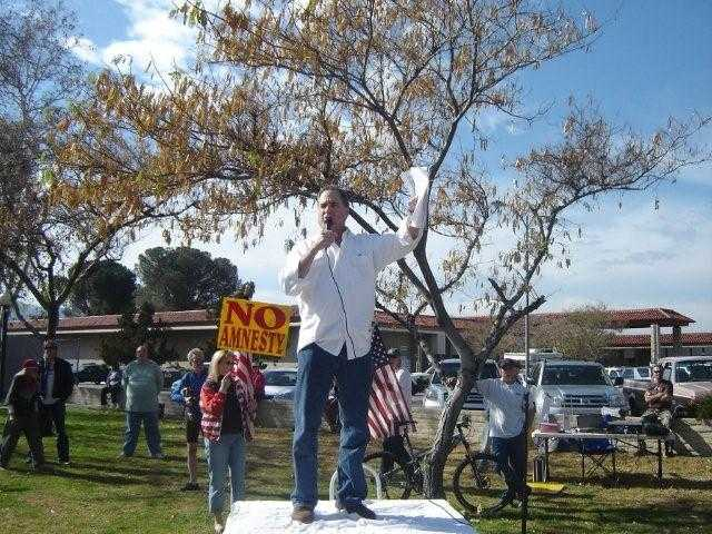 Minuteman leader Roger Gitlin addresses the crowd at the anti-illegal alien rally at the corner of Valencia Boulevard and Magic Mountain Parkway on Saturday.