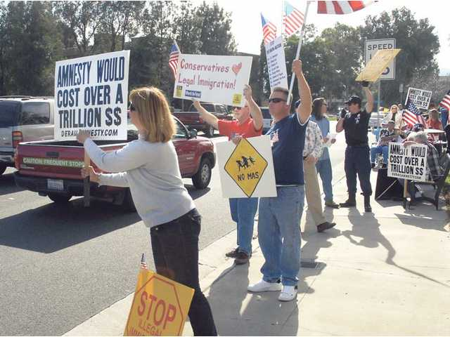 Protesters at an anti-illegal alien rally hold signs as cars pass by the intersection of Valencia Boulevard and Magic Mountain Parkway on Saturday.