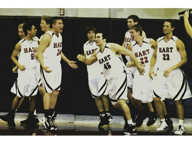 The Hart boys basketball team celebrates Friday night at Hart High after defeating Valencia 75-70 in a Foothill League contest.