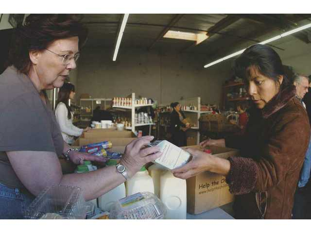A volunteer at the Hunger Defense Fund, at left, hands dairy products to a local woman Saturday morning at the food bank's Canyon Country location. Local residents answered President-elect Barack Obama's call for volunteers on Monday's National Day of Service early.