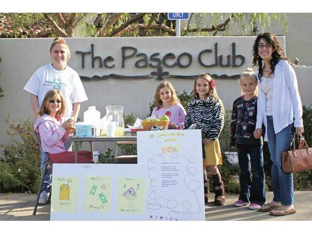 "First- and second-grade girls sell lemonade at their ""lemon-aid"" stand outside The Paseo Club on Saturday."