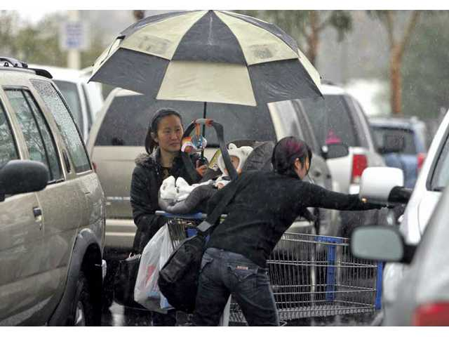Jennifer Waugh watches as her sister Madeline Yang opens the door to keep the rain from falling on 8-month-old Sadie Yang in the parking lot at Walmart in Stevenson Ranch on Tuesday.