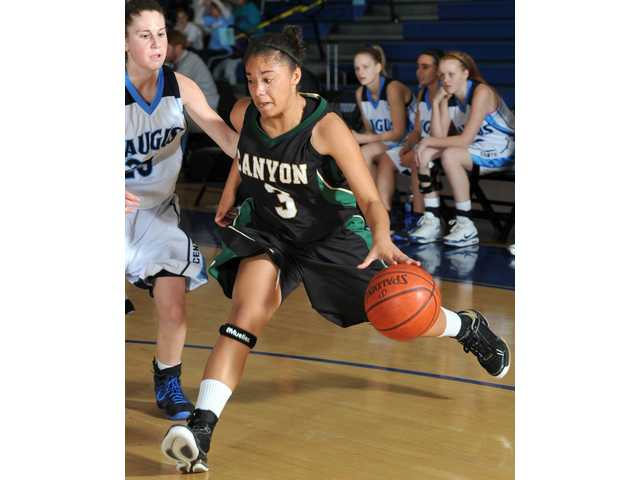 Canyon's Alexus Bryant (3) drives to the basket in the first half Tuesday as Saugus' Jordan Oster guards.