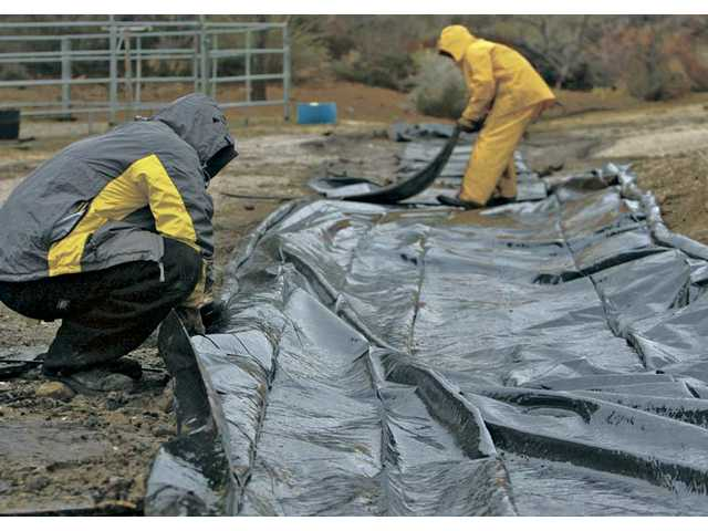 Acton residents Dusty, left, and Kyle Marshall lay down plastic sheeting as they prepare for heavy rain in an area burned in the 2009 Station Fire.