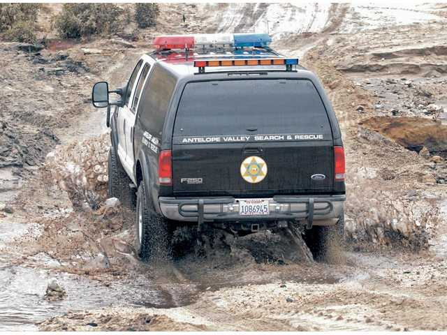 An Antelope Valley Sheriff's Search & Rescue vehicle splashes through a natural riverbed that crosses the only open access road to an area in Acton burned in the 2009 Station Fire. Officers were on their way to notify residents of a mandatory evacuation on Wednesday due to an expectation of heavy rain and mudslides.