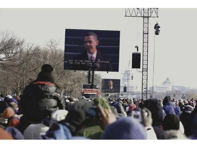 Bundled-up crowds on the National Mall snap photos as Obama makes his first speech as 44th president.