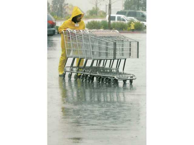 Costco employee Arthur Smith works through the rain to collect shopping carts in the Costco parking lot in Canyon Country on Wednesday.