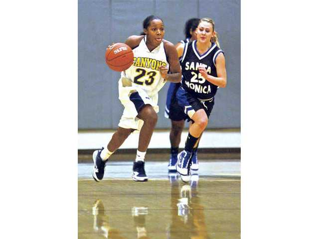 College of the Canyons freshman guard Dominique Turner (23) pushes the ball down the court as Santa Monica College's Haley Newell (25) gives chase on Wednesday at College of the Canyons.