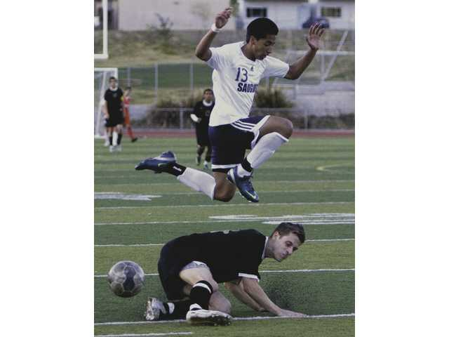 Saugus soccer player Manny Padron (13) leaps over Golden Valley's James Schlegel during Tuesday afternoon's game at Saugus High.