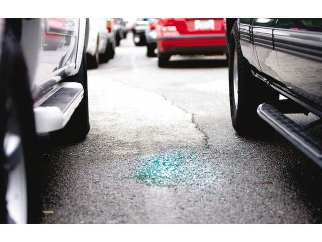 Broken glass lies between two vehicles parked at the Metrolink Soledad Canyon Station, Thursday afternoon. Numerous vehicles were broken into Wednesday evening.