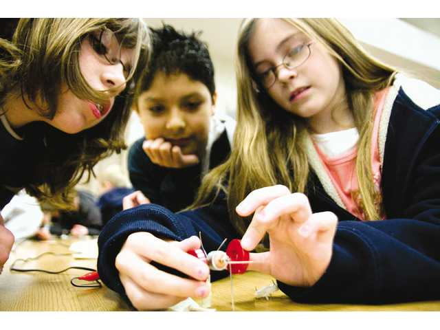 Peachland Elementary students Dakota Maxwell, Alan Franco and Emma Noland look at the motor Energy Coalition helped them build in order to further their knowledge on electromagnets and how energy is formed, Thursday morning.