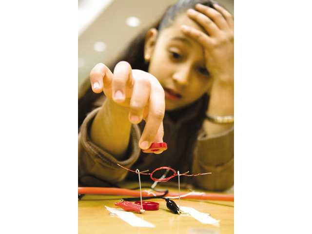 Fourth-grader Blanco Nolasco works on getting her motor working using magnets.