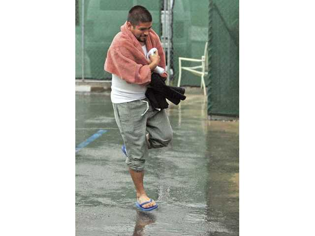 After realizing the shelter's hot water was not working in the shower area, Omar Perez runs back to the men's dormitory to avoid the rain.