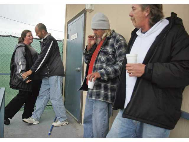 Santa Clarita Valley Emergency Winter Shelter clients hang outside the dinning room, hiding from the rain on Friday. Due to the weather the shelter remained open all day.