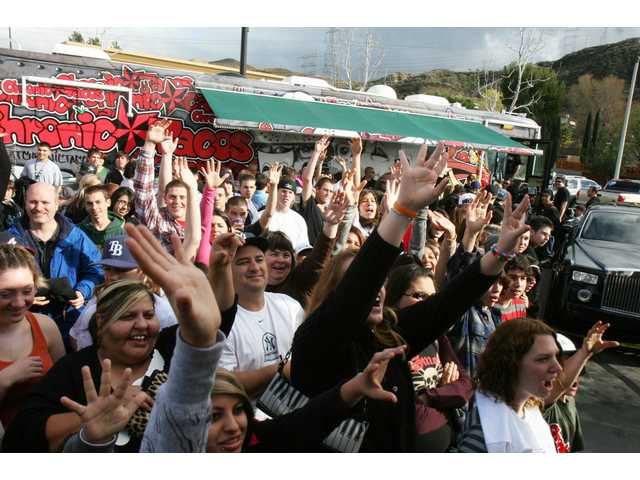 "A crowd gathers outside the Chronic Tacos tour bus to see Jason ""Wee Man"" Acuna at the grand re-opening of the Chronic Tacos restaurant in Saugus Saturday."