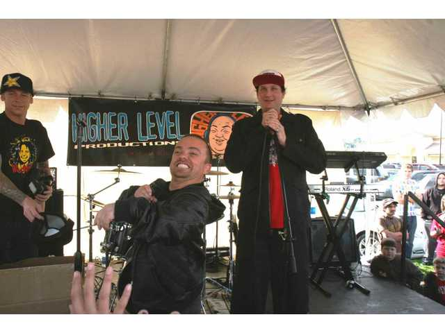 "Actor, MTV host and skateboard star Jason ""Wee Man"" Acuna (center) and Chronic Tacos founder Randy Wyner (right) hawk swag on a temporary stage in the parking lot outside the newly re-opened Chronic Tacos restaurant in Saugus Saturday. A raffle raised funds for the Yes I Can program's Summer Meltdown concert."