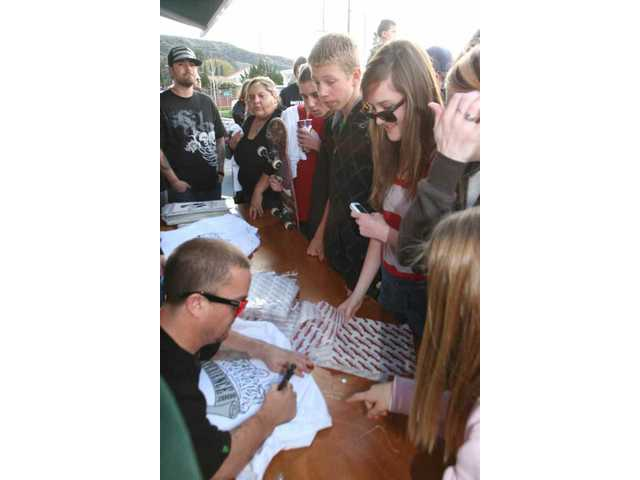 "Jason ""Wee Man"" Acuna signs autographs for some of the approximately 300 fans who jammed the Chronic Tacos parking lot in Saugus Saturday during the restaurant's grand-reopening celebration and fundraiser for Yes I Can's Summer Meltdown concert."