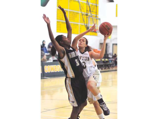 Canyon senior Kayla Michel drives to the basket as she is closely guarded by West Ranch's Brittani Walker in the first half on Tuesday at Canyon High.
