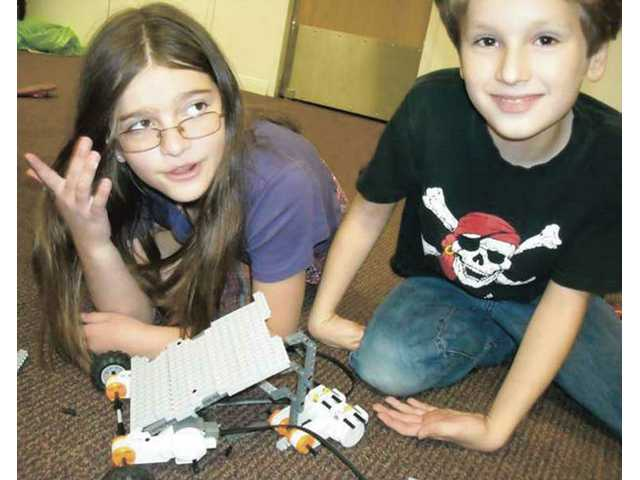 Charlotte Van Houten, left, and Audric Paris, students of Huckleberry Creative Learning Center, finish the robots they made during a Monday robotics class at the Newhall center.