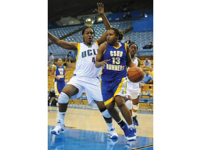 California State University, Bakersfield's Kelley Tarver (13) drives to the hoop past UCLA's Christina Nzekwe (4) on Dec. 3 at Pauley Pavilion in Los Angeles.