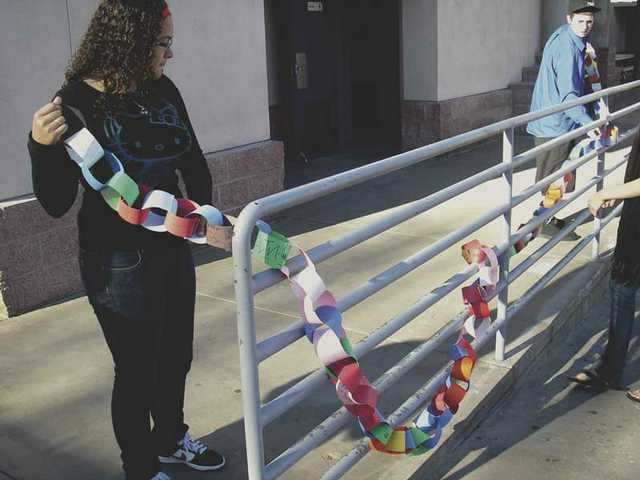 LeNees Ferguson and Troy Keith hang the Chain of Change on the Bowman campus, with student resolutions for change they want to see in their lives.
