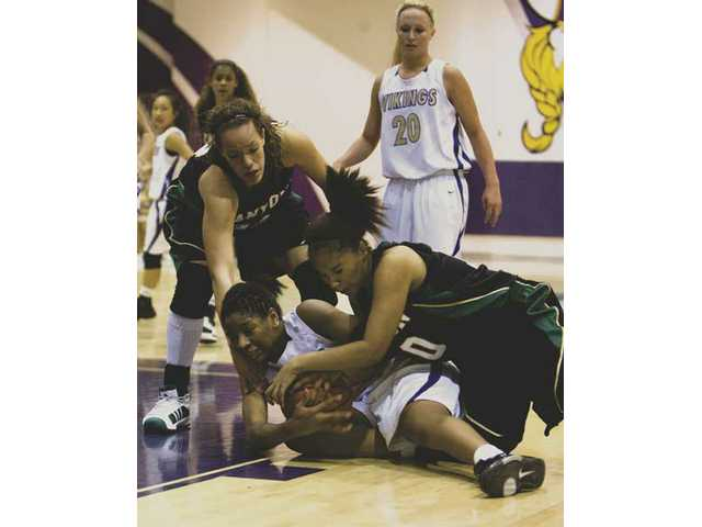 Valencia High's Starla Wright (34) battles Canyon's Kayla Michel (33), left, and Sara Ward (10) for a loose ball during Tuesday evening's game at Valencia. The Vikings won 70-57.