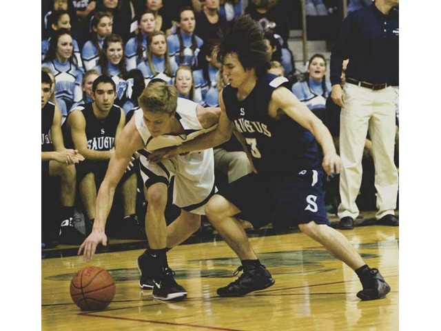 Hart's Patrick Abbott (3) battles Saugus' Mark Watanabe, right, during Tuesday night's game at Hart High. The Indians beat the Centurions 81-59.