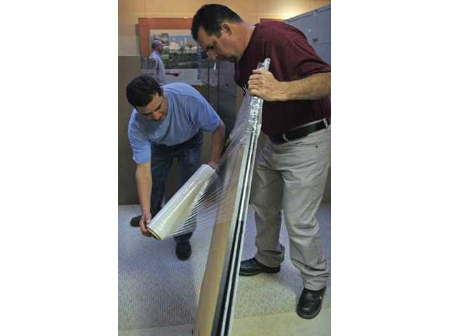 Jose Vasquez, left, and Ismael Figueroa help each other as they wrap plans during packing Wednesday at the Newhall Land & Farming offices. Movers will collect boxes and transfer them to Newhall Land's new facility this Friday.