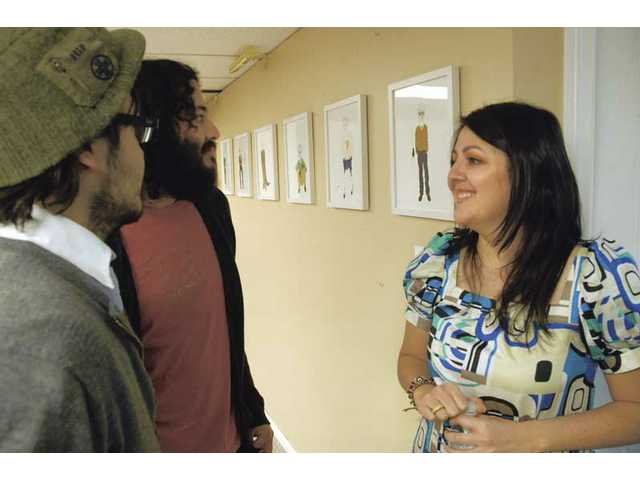 Juan Juarez, left, and his brother Miguel chat with artist Alma Juarez at an exhibit of her pen and ink artwork on display. The event featured three local musical groups and displayed a gallery of art by local artists, featuring Juarez's as the main attraction.