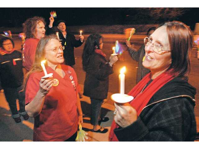 "Registered nurse Deann McEwen, left, and Santa Clarita resident Tina Grieger chant, ""we want a contract"" as they participate with about 50 people in a candlelight vigil in front of Henry Mayo Newhall Memorial Hospital on Wednesday night."