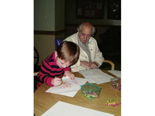 A preschooler colors for a senior at the Pacific Senior Living Center, Thursday.