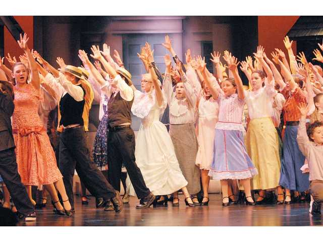 A colorful chorus sings and dances during a production number in 'The Music Man.'