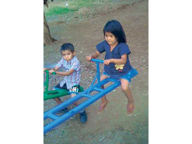 Two young children play on a teeter totter that the missions team helped install Tuesday in Masaya. The group also built rooms that were added to single-family homes.