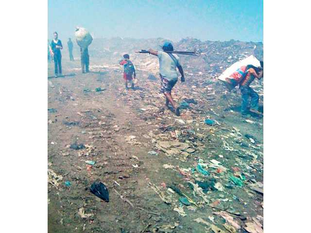 Citizens walk around the Managua dump.