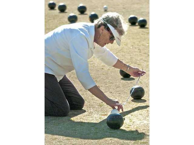"Bonnie Chisholm measures the distance of the closest ball from the white ""jack ball"" to determine the winner of the game."