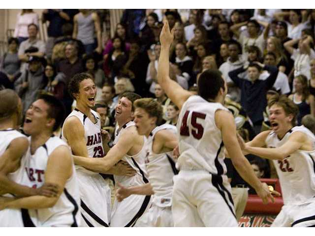 Members of the Hart High boys basketball team celebrate after knocking off Golden Valley Friday at Hart High School.