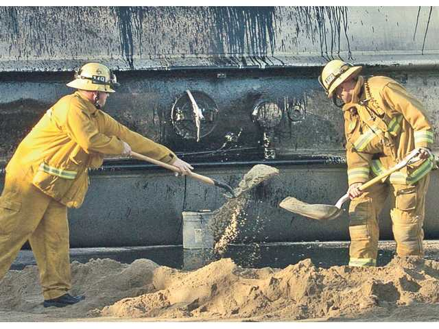 Firefighters use sand to dam a leak of crude oil from a tanker trailer that overturned on The Old Road on Saturday.