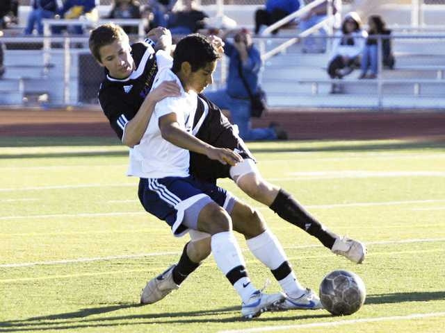 Valencia's Caleb Preston, left, battles for the ball with Saugus' Oliver Garcia Friday at Saugus High School.