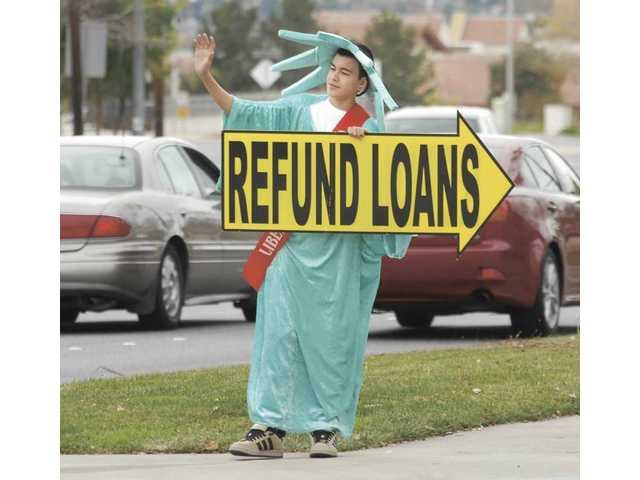 Brett Riley, 15, dressed as Lady Liberty, waves to passing cars at the corner of Bouquet Canyon and Seco Canyon roads to promote the opening of Liberty Tax Service in Santa Clarita on Sunday.