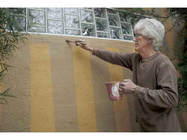 "Old Orchard homeowner Ron Gibson paints his house in stripes as a ""gentle"" protest against his homeowner's association which is forcing him to paint his house a board-approved dark brown."