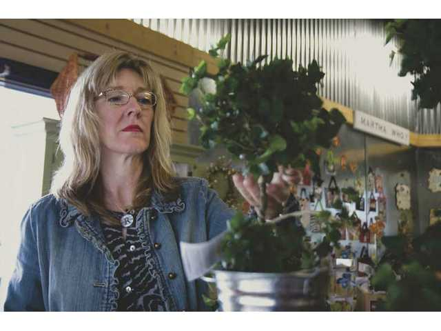 Rhonda Coleman organizes her topiary plants, one of the many decorative items available for sale at her boutique gift shop, Rooms & Blooms, in Newhall.