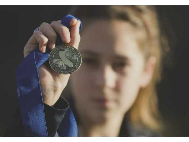 Saugus High runner Kaylin Mahoney displays the medal she won for finishing first Nov. 29 in the CIF State Division II Cross Country Championships. Mahoney was the Foothill League and CIF-SS Division II champion.